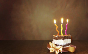 Piece of birthday chocolate cake with burning candles against brown background